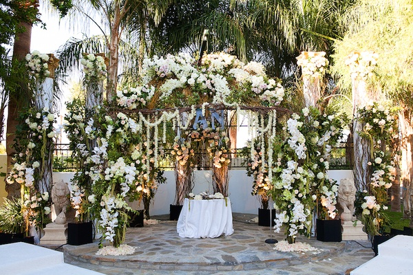Wedding flower arch with branches, green leaves, white roses, and orchids