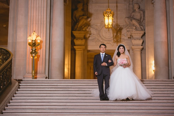Bride in a strapless Kenneth Pool dress with tulle skirt, veil, walks down stairs with her father