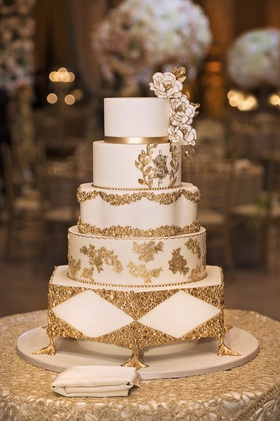Small four-tiered wedding cake with gold details and sugar flowers