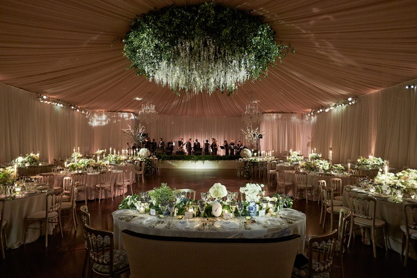 Wedding reception tented walls ceiling drapery flower chandelier dance floor live band greenery