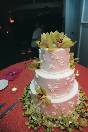 white cake covered with green orchids on top and bottom