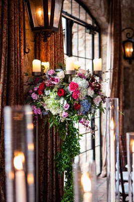 Metal candelabra wedding centerpiece with greenery, pink red roses, blue hydrangeas