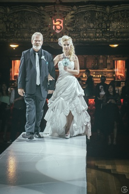 Bride walking down catwalk at theater with father of bride