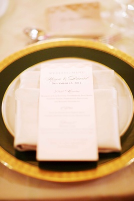Wedding reception place setting gold rim charger plate dinner menu on top of napkin with calligraphy