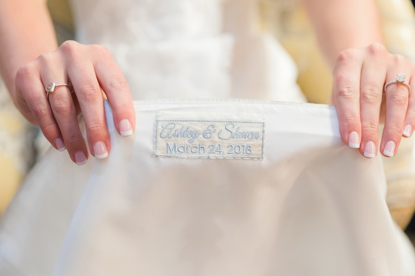 pale blue embroidery of names and wedding date on lining of wedding dress