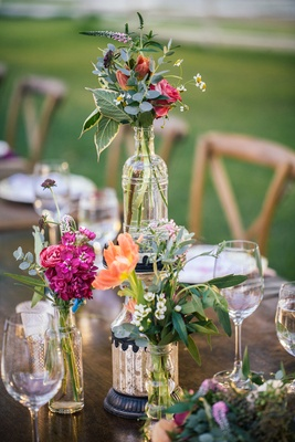 Outdoor bohemian wedding reception table with decorative vases, bottles with bundles of pink flowers