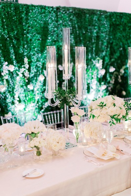 wedding head table in front of hedge wall with ivory flowers and crystal candelabra with greenery