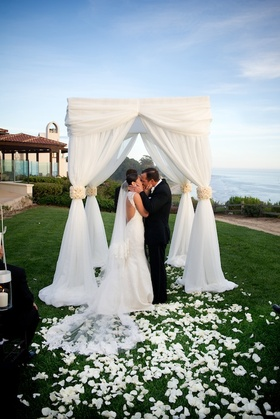 Bride and groom kiss under white wedding canopy