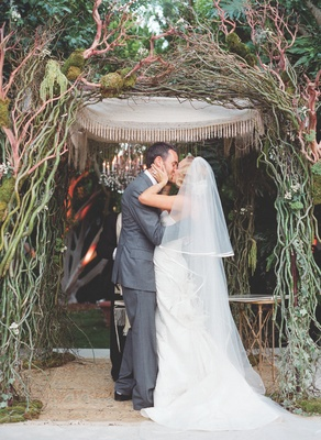 Bride in a Carolina Herrera gown and veil kisses groom in grey suit under a chuppah