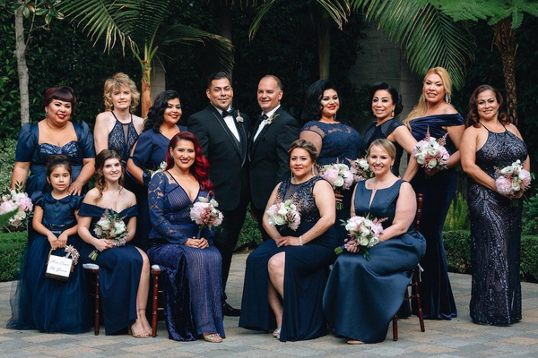 same-sex wedding inspiration, gay wedding with large group of groomsmaids in navy dresses