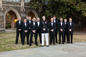 Groom in dress blues uniform and tuxedo groomsmen