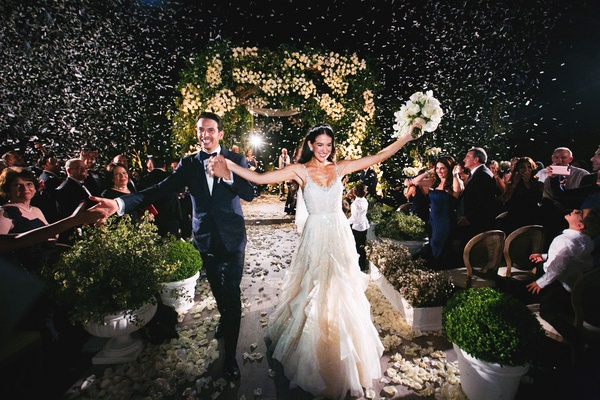 bride and groom recession wedding ceremony outdoor confetti in air dark night ceremony photo