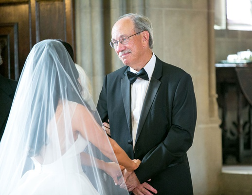 Bride showing father of bride wedding dress for first time father in bow tie and suit