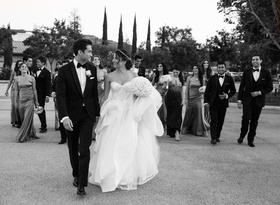 Black and white photo of bride in Monique Lhuillier dress and groom with wedding party