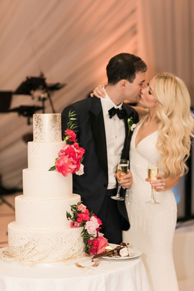 bride and groom kiss with champagne at wedding cake white gold splatter design bright pink flowers
