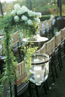 Etched candleholder hanging from shepherd hook at ceremony