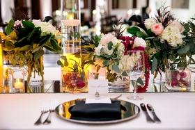 Wedding reception table with mirror runner orchids and floating candles, white pink burgundy flowers