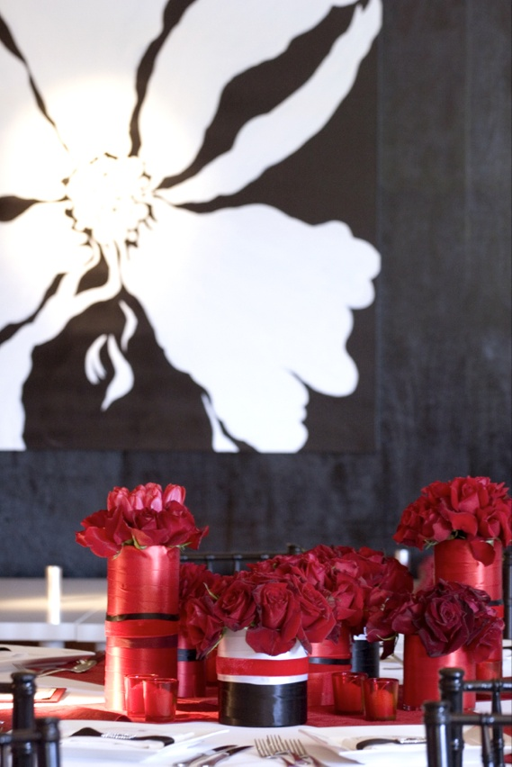 Black and white flower painting on wall and red centerpieces on table