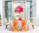 vibrant fall inspired tablescape orange pink purple champagne color chair covers pom poms