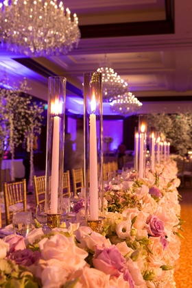 Long wedding reception head table with white, purple roses, mint hydrangeas, taper candles on gold