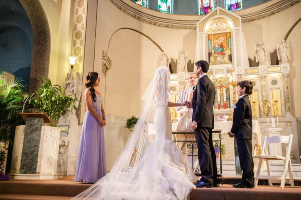 Bride in Vera Wang wedding dress with groom at altar of The Shrine of Our Lady of Pompeii