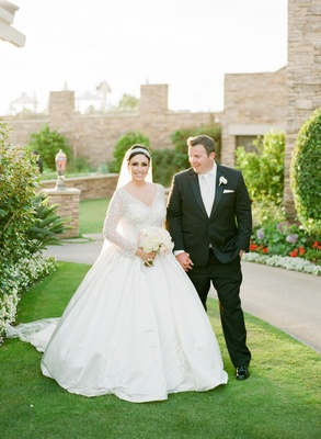 Bride in long-sleeve ball gown with tuxedo groom outside