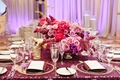 pink and purple floral arrangements centerpieces purple linens glass plateware reception