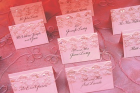 Escort cards decorated with lace and sequins