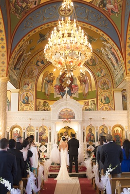 Bride in Inbal Dror dress and groom in tuxedo at altar of Ascension Greek Orthodox Church