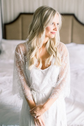 bride with long blonde hair curls pink manicure in sheer white robe lace pretty