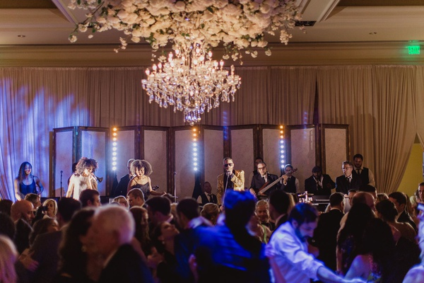 wedding reception live band at reception ballroom chandelier flower ceiling singer performers