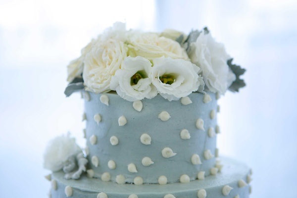 top tier couples blue wedding cake white polka dots flowers on top