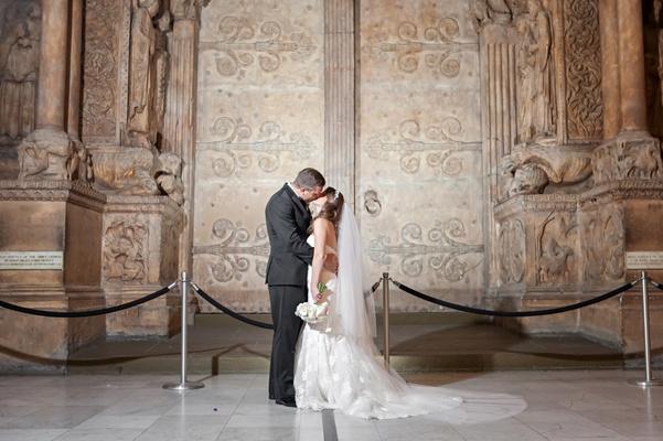 Bride and groom next to ancient door on display