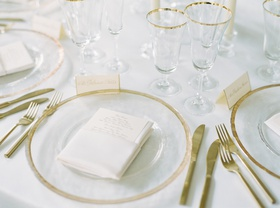 clear charger plates rimmed with gold, gold flateware at wedding reception