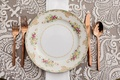 Rose gold forks knife spoon with pink yellow green flower print china plate white grey linen wedding
