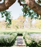 ojai valley inn wedding ceremony with aisle lined by greenery and flowers