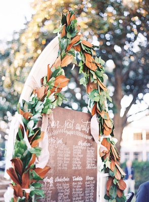 Wood seating chart with calligraphy names and magnolia leaf arch with white tulle ribbon