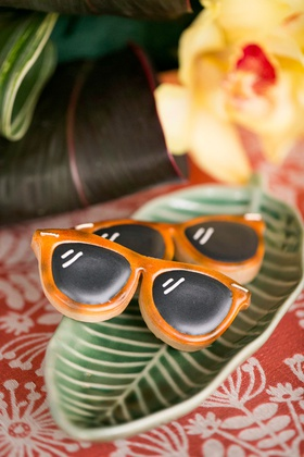 tropical wedding inspiration shoot with palm plate and orange rayban sunglasses cookies