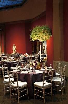 Wedding reception with dark tablecloths and a tree