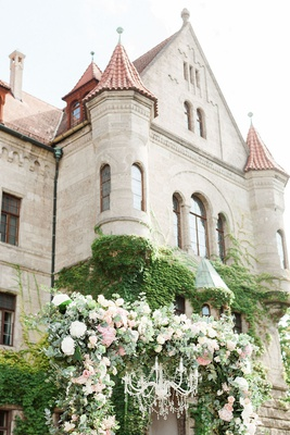 wedding ceremony germany castle venue greenery white pink flowers chandelier arch chuppah