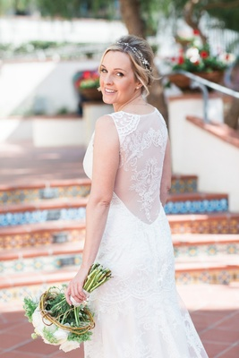 Bride in a sleeveless Claire Pettibone dress with illusion back, embroidery, white bouquet