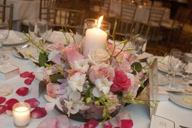 Wedding reception centerpiece of pink roses and white orchids with a central candle