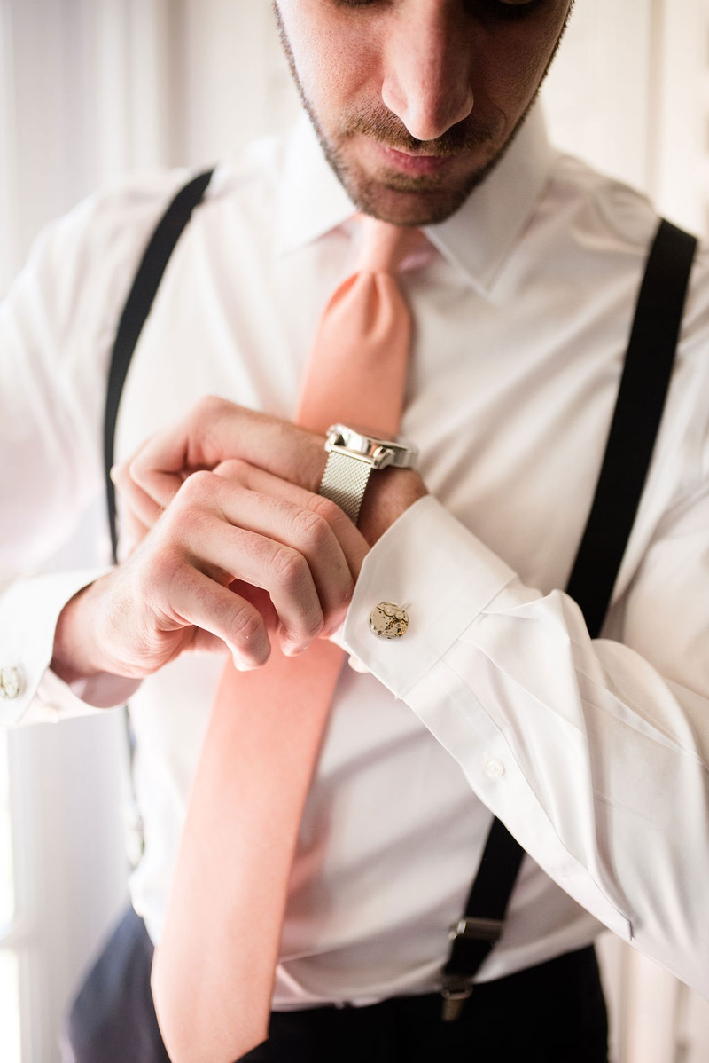 wedding photo of groom getting ready suspenders pink tie silver watch and cuff links