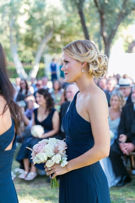 Bridesmaid in a one shoulder dark blue Monique Lhuillier dress with curled updo, rose bouquet