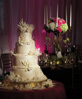 wedding cake decorated with seashells and coral