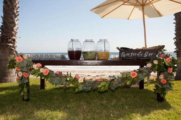 Wood rustic table with flower greenery garland margarita bar wood sign umbrella margaritas in drink