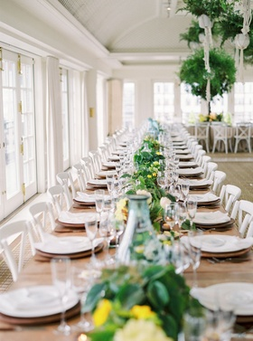 Wedding reception wood table white chairs with long greenery flower runner yellow blooms simple
