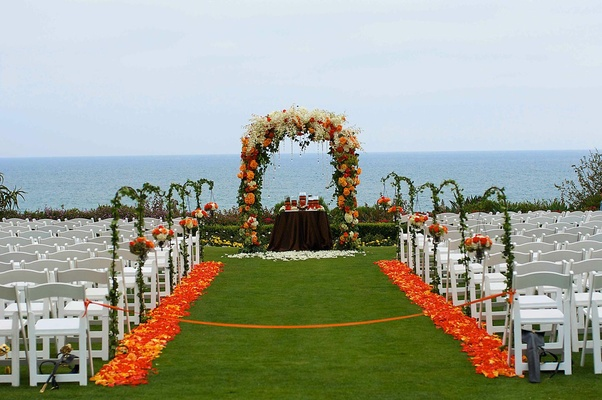 Orange floral arch and petal-lined aisle