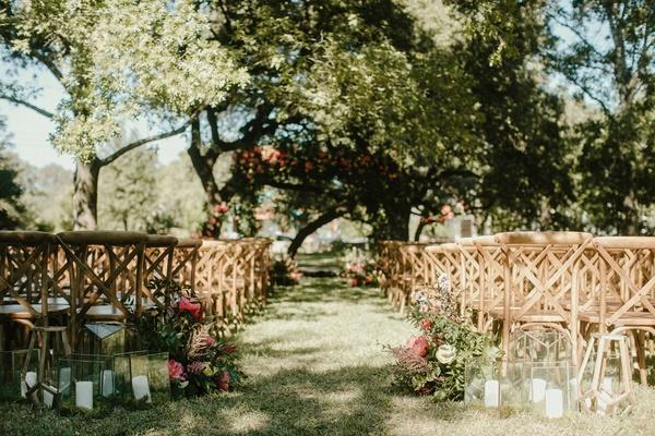 wedding reception wood vineyard chairs candle lanterns terrarium greenery trees blue sky