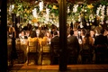 Wedding reception view of guests at long tables from outside of venue space high centerpieces